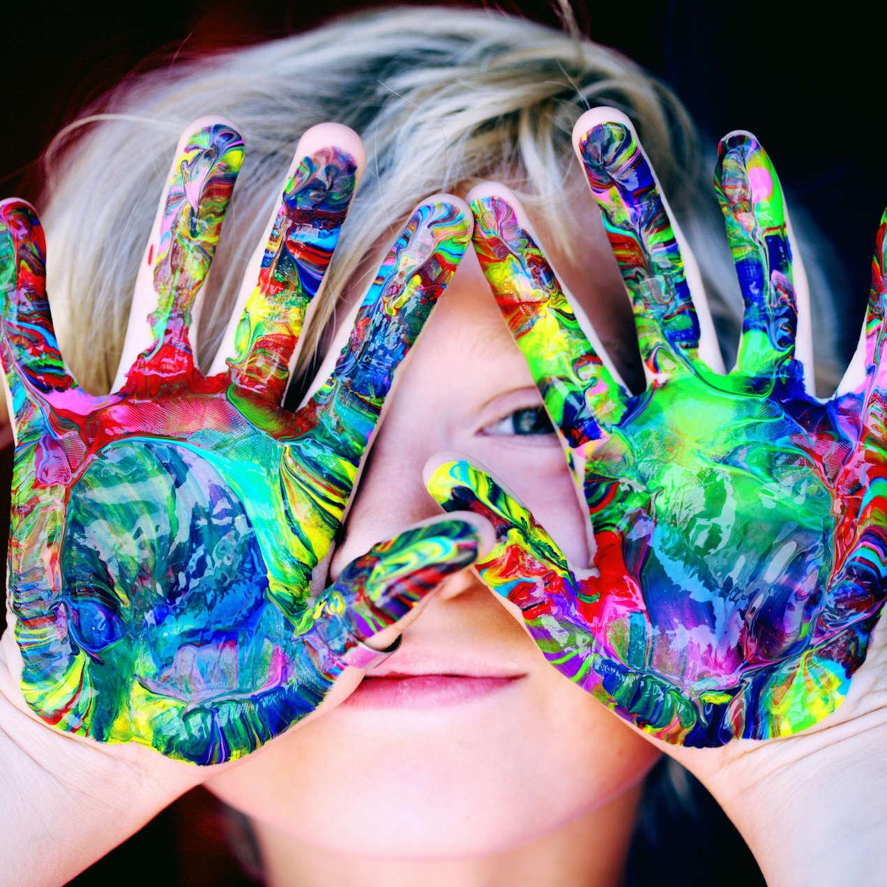 enfant avec des mains pleines de peinture