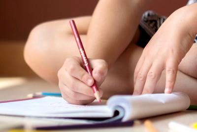 enfant écrivant dans un cahier