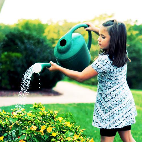 Jeune fille qui arrose des plantes